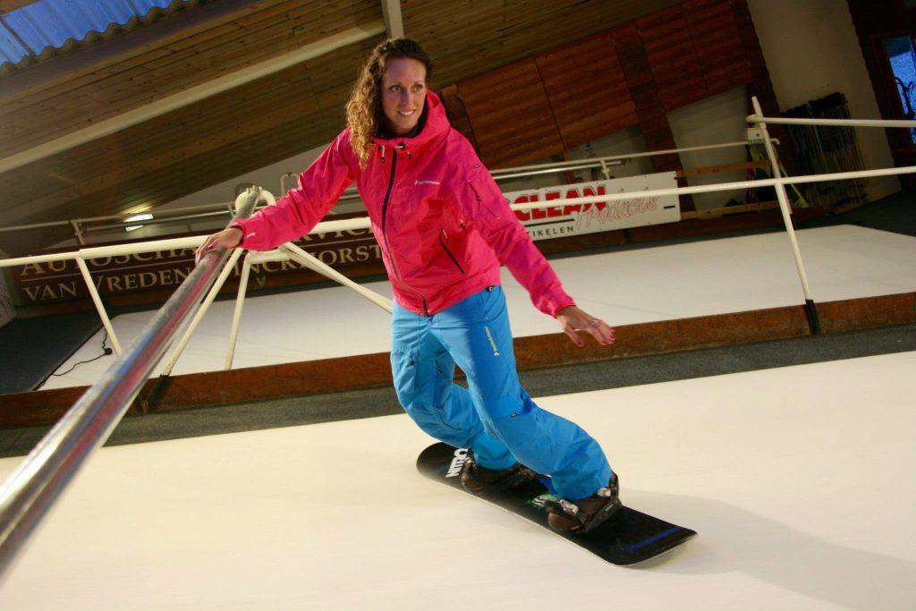 Vrouw op snowboard tijdens indoor snowboardles