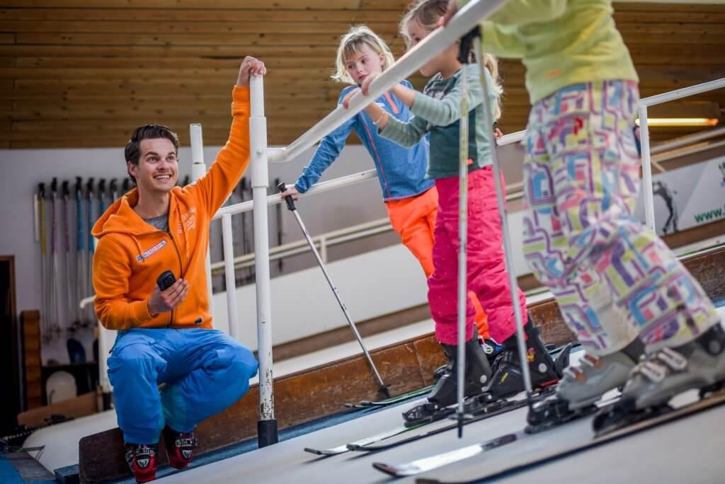 Kinderen die skiles krijgen op indoor skibaan