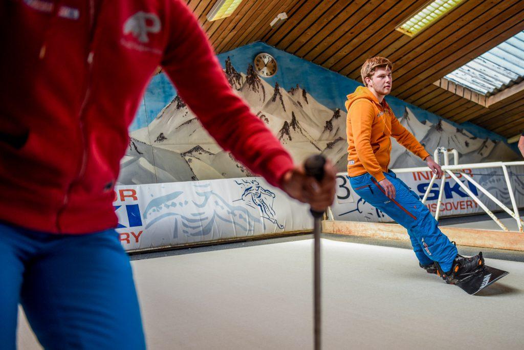 Skidiscovery leraar op een snowboard op indoor skibaan